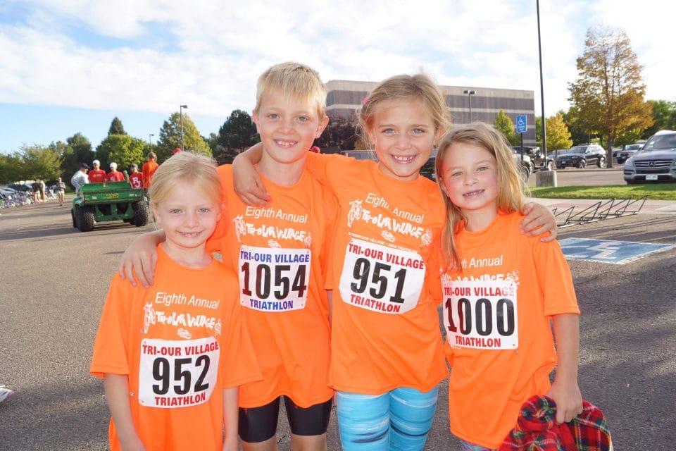 four kids smiling at greenwood village kids triathlon