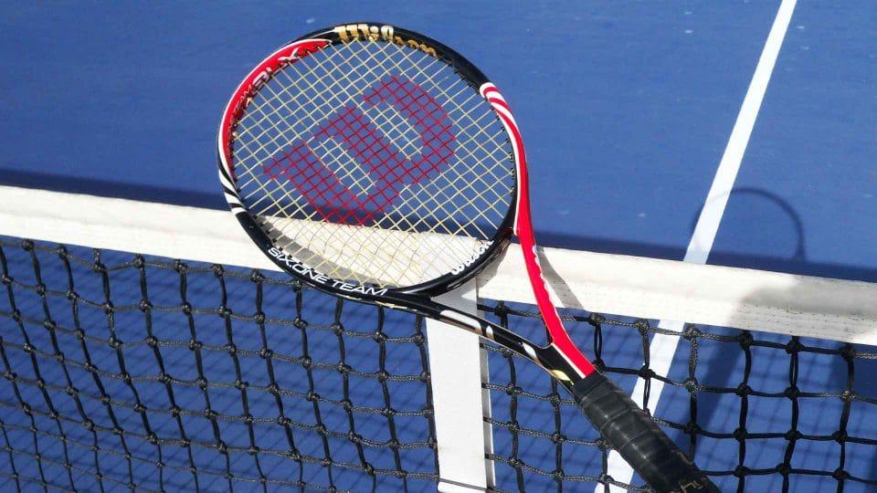 tennis racquet on tennis net